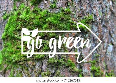 Inspirational banner Go Green banner decorated hand drawn leave, index on the green moss tree bark background. Quote for Earth day, ecological sign, protect nature label. Photo for care our planet