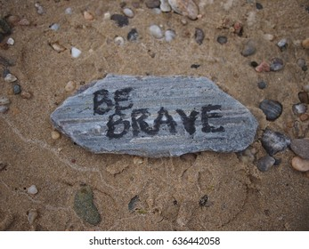 """Inspirational """"Be Brave"""" engraving on a stone at the beach"""