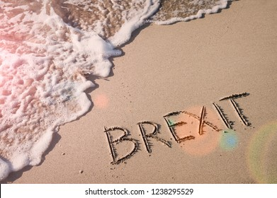 Inspirational Brexit message handwritten in smooth sand with sunny lens flare above incoming waves