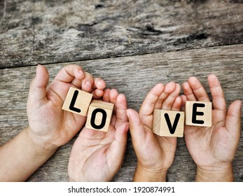 Inspirational Concept - LOVE text on wooden blocks with palms background. Stock photo.
