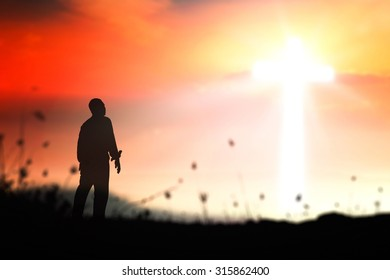 Inspirational concept: Silhouette human standing for praising God over blurred the cross on mountain sunset background