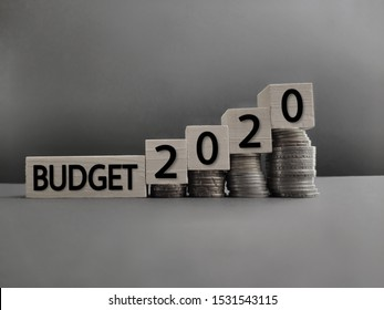 inspirational and conceptual - budget 2020 on wooden blocks with coins stack background. Stock photo