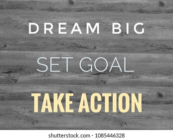 Inspirational motivating quote. Dream big, set goal, take action on black and white wooden background