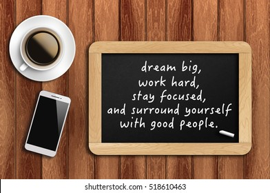 Inspirational motivating quote on chalkboard with coffee, phone and wooden background. Dream big, work hard, stay focused, and surround yourself with good people.