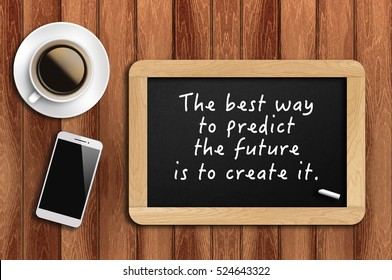 Inspirational motivating quote on chalkboard with coffee, phone and wooden background. The best way to predict the future is to create it.