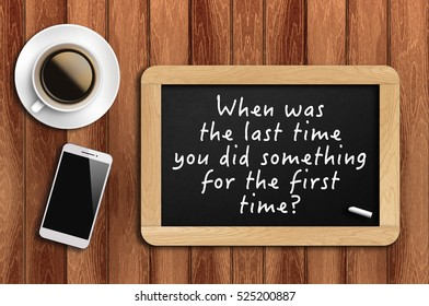 Inspirational motivating quote on chalkboard with coffee, phone and wooden background. When was the last time you did something for the first time?