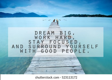 Inspirational motivating quote on long exposure of wooden jetty at sea facing island with cloud and sky at twilight. Dream big, work hard, stay focused, and surround yourself with good people.