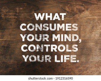 """Inspirational motivating quotes """"what consumes your mind, controls your life"""" written on blurry grunge wooden background."""
