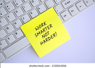 Inspirational and motivation life quote on paper note attached to keyboard - Work harder not smarter.