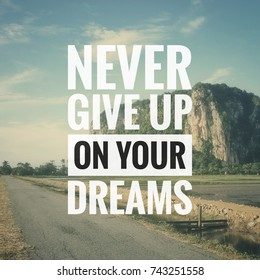 Inspirational motivation quote NEVER GIVE UP ON YOUR DREAMS on nature, mountain, road, paddy field, blue sky clouds background.