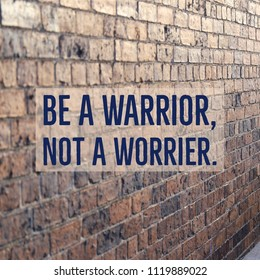 "Inspirational motivational quote ""Be a warrior, not a worrier."" on beautiful brick wall background."