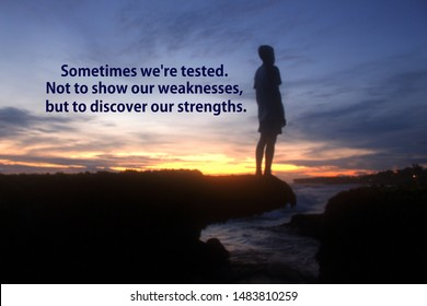 Inspirational motivational quote - Sometimes we are tested. Not to show our weakness, but to discover our strengths. With blurry silhouette of young boy stands alone on sea rock. Dramatic sunset sky.