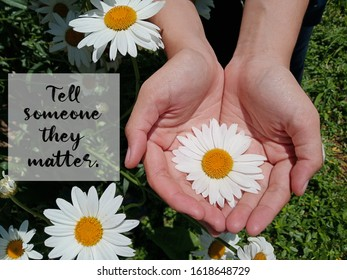 Inspirational motivational quote - Tell someone they matter. With background of big white daisy flower blossom in young woman hand in the garden. Words of kindness wisdom concept.