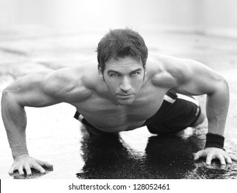 Inspirational portrait of a muscular fit man doing push-ups on wet cement