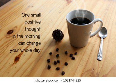 """Inspirational positive quote """" One small positive thought in the morning can change your whole day."""" with hot coffee with steam in a white cup and coffee bean on the wooden desk."""