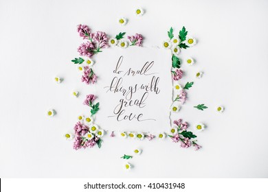 "inspirational quote ""Do small things with great love"" written in calligraphy style on paper with wreath frame with lilac and chamomile isolated on white background. flat lay, overhead view, top view"