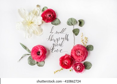 "inspirational quote ""Do small things with great love"" written in calligraphy style on paper with pink, red roses, ranunculus, white tulip and leaves isolated on white background. Flat lay, top view"