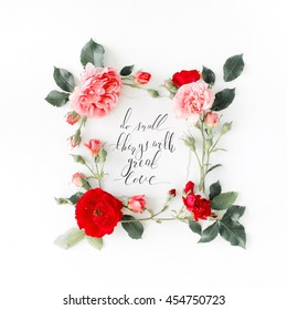 "inspirational quote ""do small things with great love"" written in calligraphy style on paper with pink, red roses, chamomiles and leaves isolated on white background. Flat lay, top view"