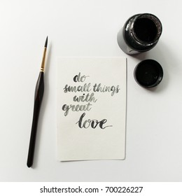 "Inspirational quote ""do small things with great love"", ink, paint brush on a white background. Artist workspace"
