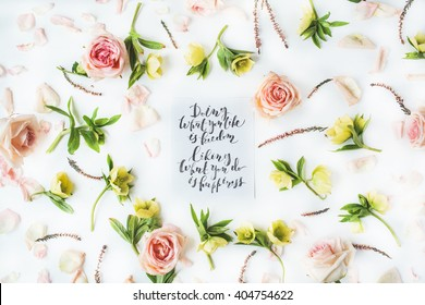 "inspirational quote ""doing what you like is freedom, liking what you do is happiness"" written in calligraphy style on paper with pink roses and yellow flowers on white background. Flat lay, top view"