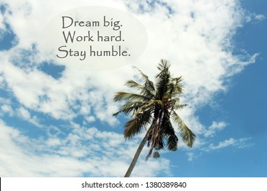 Inspirational Quote- Dream big. Work hard. Stay Humble. With single coconut palm tree under the beautiful white clouds and blue sky at day time.