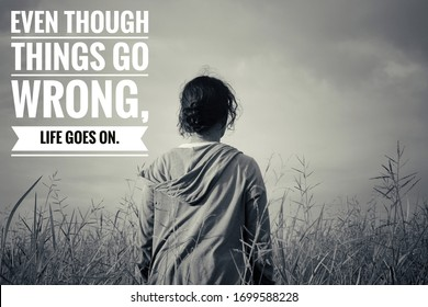 Inspirational quote - Even though things go wrong, life goes on. With young woman in the field against blue sky and meadow in vintage style black and white. Motivational words with abstract background