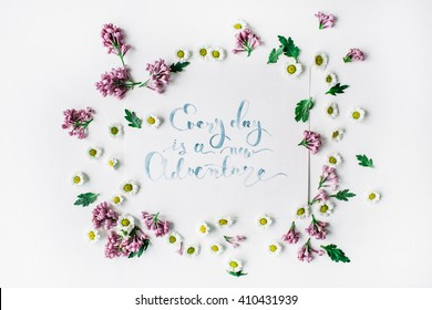 "inspirational quote ""everyday is a new adventure"" written in calligraphy style on paper with wreath frame with lilac and chamomile isolated on white background. flat lay, overhead view, top view"