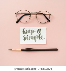 "Inspirational quote ""keep it simple"", glasses, paint brush on a pale pink pastel background. Artist workspace"