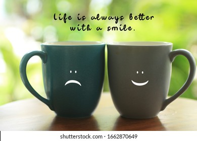 Inspirational quote - Life is always better with a smile. With two cups of tea or coffee couple on fresh green bokeh background. Sad and happy smiling face on mugs, cheer  up your day concept.