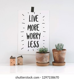 "Inspirational quote ""live more, worry less"". Cactus in clay pots over white background."