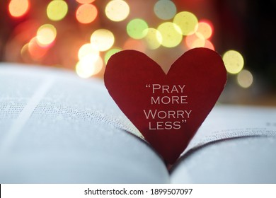 Inspirational quote on a red heart - Pray more, worry less. Spiritual text message on an open bible book page with colorful bokeh lights background. Faith, hope, love and believe in God concept.