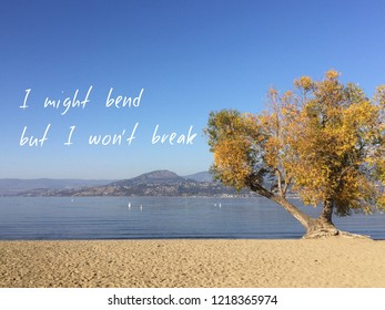 Inspirational quote on scenic autumn lake and mountains landscape with clear blue sky. Big tree with golden leaves on sandy beach leaning over lake. I might bend but I won't break.