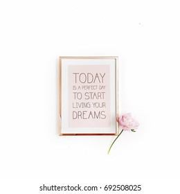 "Inspirational quote ""Today is a perfect day to start living your dreams"". Minimal golden photo frame and pink peony flower on white background. Flat lay, top view."