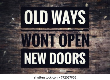 inspirational quote-old ways wont open new doors.with blurred wooden background.