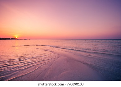 Inspirational sea and sky background. Calming and relaxing colors and soft waves on sandy beach. Tropical sunset landscape