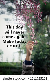 Inspirational words - This day will never come again. Make today count. Motivational quote concept with hand holding a pink flower on blurry sky and tree background.