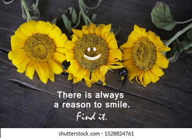 Inspirational words with yellow sun flowers - There is always a reason to smile. Find it. Three beautiful sunflowers blossom on the rustic wooden table background. Smiling face emoticon on flower.