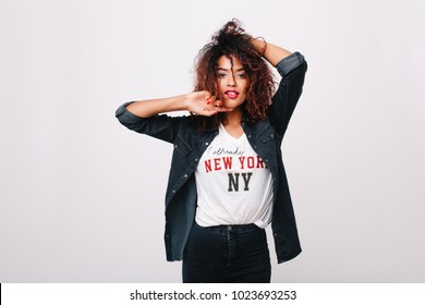 Inspired african girl with shiny dark eyes posing with hands up on white background. Indoor portrait of fashionable black young woman with pretty face wears denim jacket.