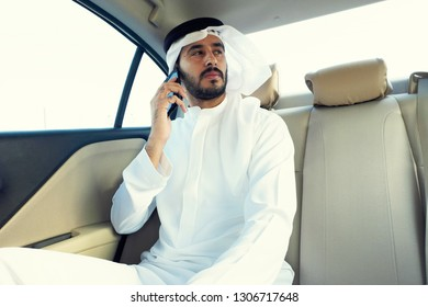 Inspired Arabic man on the phone talking about business while inside a car