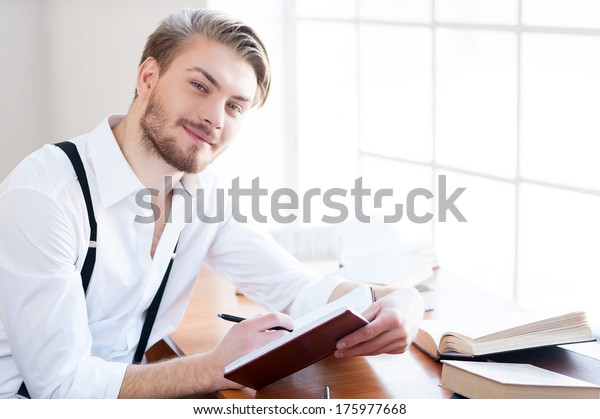 Inspired author. Handsome young man in shirt and suspenders writing something in note pad and smiling at camera while sitting at his working place