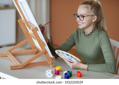 Inspired blonde teen girl with brush and palette painting and smiling, home interior. Creative schooler enjoying her new hobby, painting still life, side view. Teenagers lifestyle concept