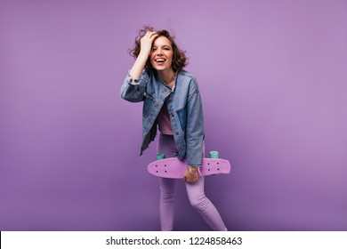 Inspired caucasian woman in casual attire expressing good emotions. Carefree curly girl with skateboard standing on violet background.