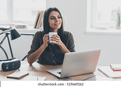 Inspired with cup of fresh coffee. Thoughtful young woman in smart casual wear holding coffee cup and looking away with smile while sitting at her working place in office