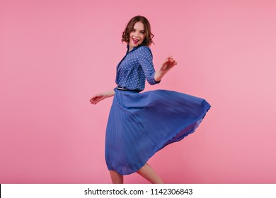Inspired female model in midi skirt dancing with pleasure on pink background. Studio portrait of caucasian sensual girl in trendy blouse having fun.