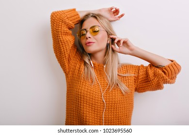 Inspired girl in oversize wool sweater relaxing with eyes closed, leaning to the wall. Indoor portrait of dreamy blonde woman in glasses and earphones isolated on white background.