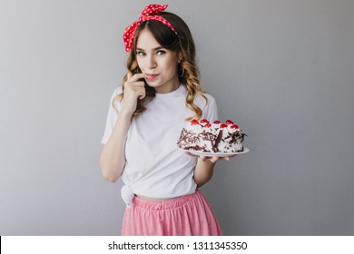 Inspired girl with wavy hair tasting birthday cake. Studio photo of enchanting female model with pie posing on gray background.