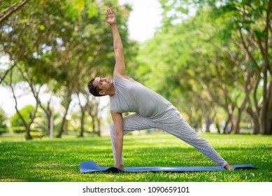Inspired Indian man doing yoga asanas in city park. Young citizen exercising outside and standing in yoga side angle pose. Fitness outdoors and life balance concept
