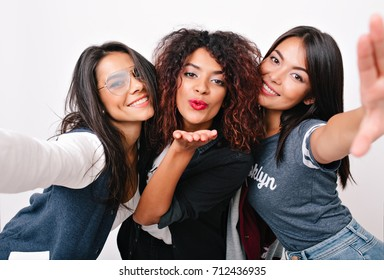 Inspired latin girl in glasses taking photo of herself while fooling around with university friends. Romantic curly black woman sending air kiss for selfie with charming ladies.