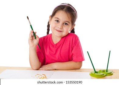 Inspired little girl with paintbrush on the table, isolated on white