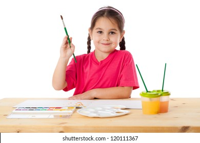 Inspired little girl with paintbrush and watercolors at the table, isolated on white